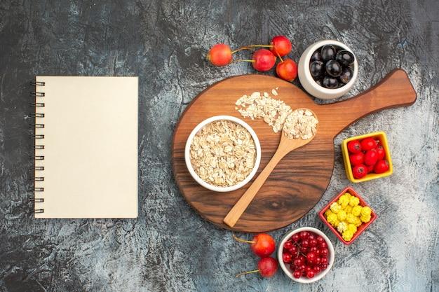 Widok z góry z bliska jagody notebook wiśnie płatki owsiane i łyżka na pokładzie jagody żółte cukierki