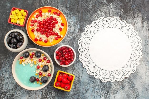 Widok z góry z bliska jagody winogrona wiśnie i czereśnie czerwone porzeczki granat cukierki owsiane koronki serwetka