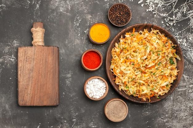 Widok z góry z bliska kapusta z marchewką talerz kapusty deska do krojenia miski przypraw