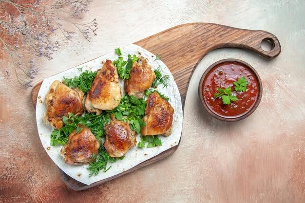 Widok z góry z bliska kawałki kurczaka z ziołami na lawaszu na pokładzie miska sosu