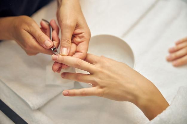 Widok z góry z bliska kobiecych dłoni, podczas gdy profesjonalista usuwa naskórek nad miską wodą