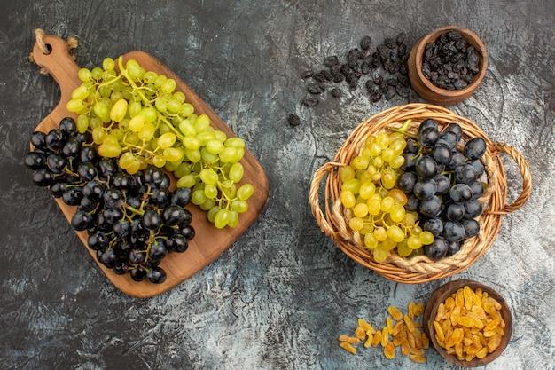 Widok z góry z bliska kosz winogron i deska do krojenia winogron między dwiema miskami suszonych owoców
