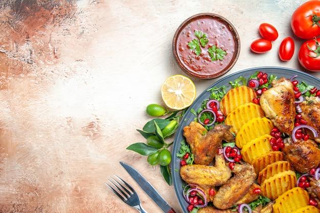 Widok z góry z bliska kurczak skrzydełka z kurczaka z ziemniakami zioła pomidory cytryna widelec nóż