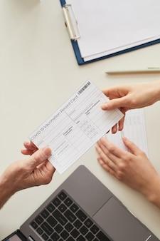 Widok z góry z bliska lekarza podającego kartę szczepień przeciw covid pacjentowi przez stół w klinice, skopiuj miejsce