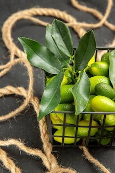 Widok z góry z bliska lina z owoców cytrusowych obok owoców cytrusowych w koszu