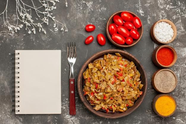 Widok z góry z bliska naczynie i przyprawy biały notatnik widelec talerz fasoli i kolorowych przypraw na czarnym stole
