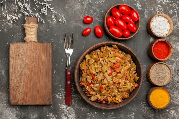 Widok z góry z bliska naczynie i przyprawy drewniana deska do krojenia talerz z fasolką szparagową widelcem i kolorowymi przyprawami na czarnym stole