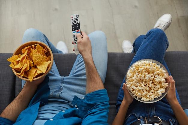 Widok z góry z bliska nierozpoznawalnej pary, oglądając telewizję razem, siedząc na przytulnej kanapie w domu i delektując się przekąskami