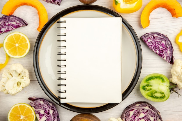 Widok z góry z bliska notatnik na okrągłym talerzu pokrój warzywa różne przyprawy w małych miseczkach na powierzchni drewnianych