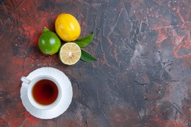 Widok z góry z bliska owoce cytrusowe limonki cytryny z liśćmi filiżanka herbaty