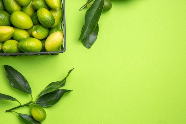 Widok z góry z bliska owoce cytrusowe zielone liście i kosz owoców cytrusowych na stole