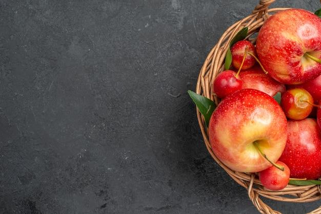 Widok z góry z bliska owoce, czereśnie i jabłka w drewnianym koszu na ciemnym stole