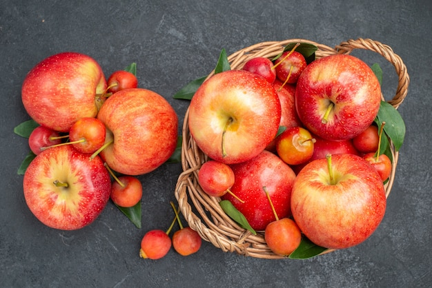 Widok z góry z bliska owoce czerwono-żółte jabłka i jagody z liśćmi w koszu