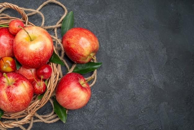 Widok z góry z bliska owoce drewniany kosz jabłek i wiśni z liśćmi