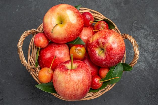 Widok z góry z bliska owoce drewniany kosz z wiśniami i jabłkami