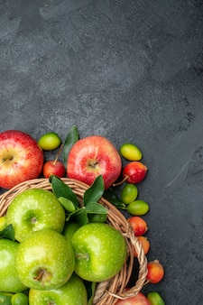 Widok z góry z bliska owoce drewniany kosz z zielonymi jabłkami i czerwonymi jabłkami wiśnie i czereśnie owoce cytrusowe