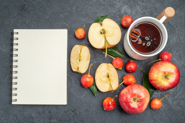Widok z góry z bliska owoce filiżanka herbaty jabłka wiśnie z liśćmi biały notatnik