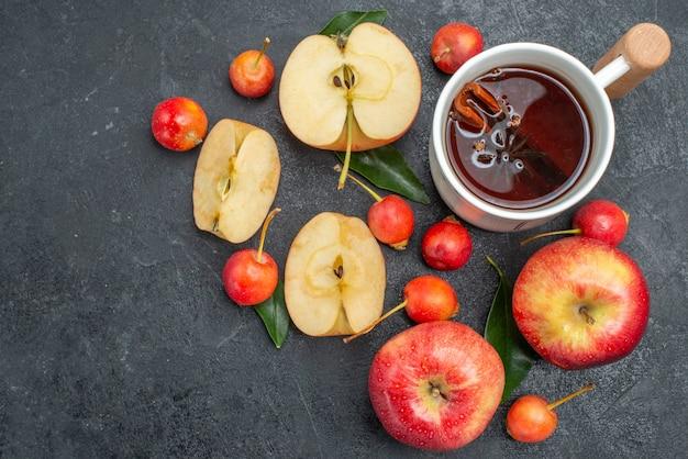 Widok z góry z bliska owoce jabłka jagody z liśćmi obok filiżanki herbaty