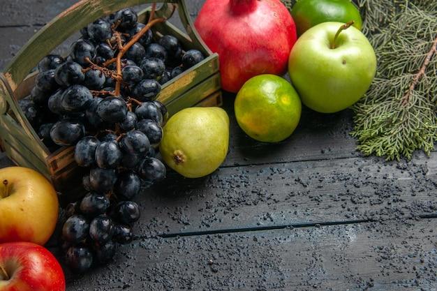 Widok z góry z bliska owoce winogrona w drewnianym pudełku jabłka granat gruszki limonki obok świerkowych gałęzi na ciemnym stole