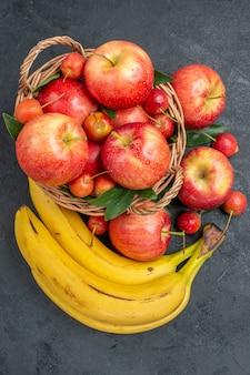 Widok z góry z bliska owoce wiśnie i czereśnie jabłka w koszyku banany
