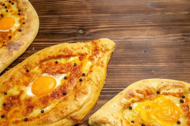 Widok z góry z bliska pieczone pieczywo jajeczne świeże z pieca na brązowym drewnianym biurku ciasto jajko chleb bułka śniadanie