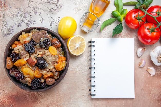Widok z góry z bliska pilaw pilaw butelka oliwnych pomidorów czosnku z szypułkami biały notatnik