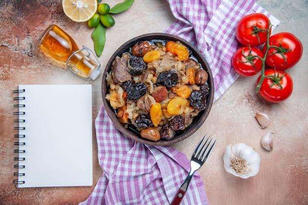 Widok z góry z bliska pilaw pilaw na obrus pomidory czosnek cytryna olej widelec biały notatnik