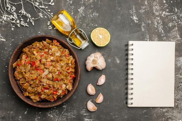Widok z góry z bliska płyta fasolki szparagowej butelka oleju czosnek cytryna biały notatnik obok talerz fasolki szparagowej z pomidorami na czarnym stole