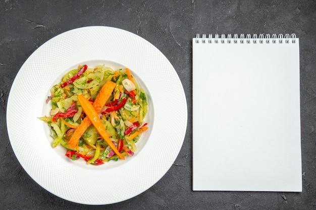 Widok z góry z bliska płyta sałatkowa z apetyczny sałatka z marchewką papryka biały notatnik