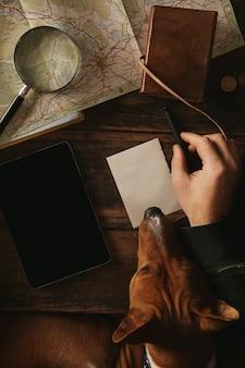 Widok z góry z bliska podróżnik przygodowy pisze plan nowej wyprawy. jego ciekawy pies rasy basenji spokojnie siedzi na kolanach