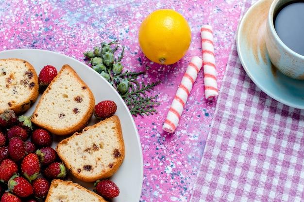 Widok z góry z bliska pokrojone pyszne ciasta ze świeżymi czerwonymi truskawkami i filiżanką kawy na różowym biurku ciasto upiec ciasto biszkoptowe słodki cukier