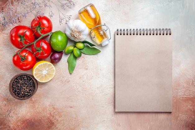 Widok z góry z bliska pomidory olej owoce cytrusowe pomidory cebula czosnek czarny pieprz śmietana notebook