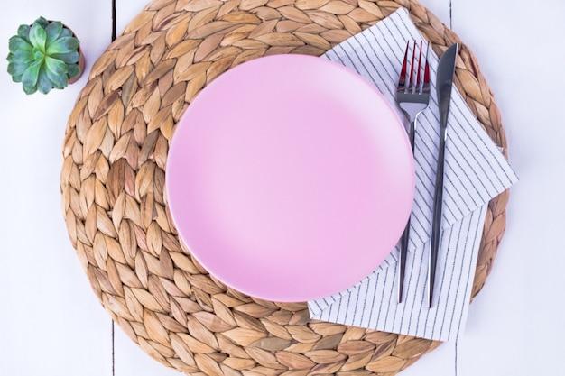 Widok z góry z bliska porcji pustych różowych talerzy, noża i widelca na ekologicznej serwetce słomy. selektywna ostrość. makieta, minimalizm.
