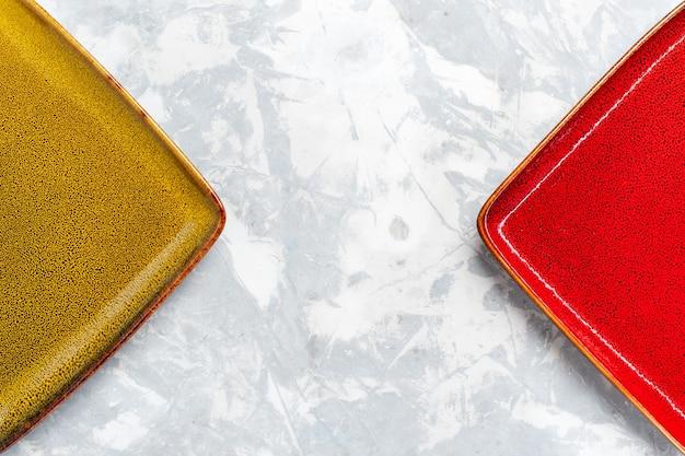 Widok z góry z bliska puste kwadratowe talerze w kolorze czerwonym i oliwkowym na białej powierzchni płyta kuchenna kolor sztućców do żywności