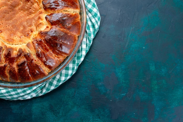 Widok z góry z bliska pyszne pieczone ciasto okrągłe utworzone słodkie wewnątrz szklanej patelni na jasnoniebieskim tle.