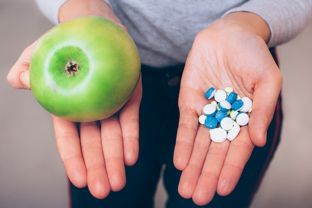 Widok z góry z bliska ręce pokazujące jabłko w jednej ręce i pigułki farmaceutyczne w drugiej. kobieta pokazuje sposoby na zwiększenie odporności w sposób naturalny lub farmaceutyczny.