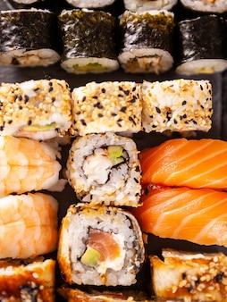 Widok z góry z bliska rolki sushi na czarnym tle kamienia