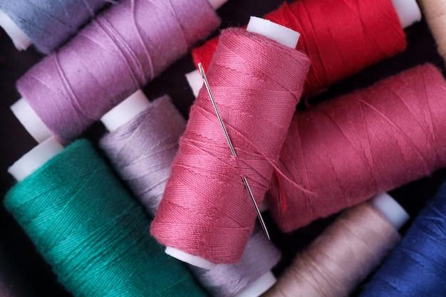 Widok z góry z bliska rozrzuconych kolorowych nici bawełnianych z igłą