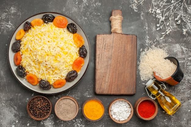 Widok z góry z bliska ryż deska do krojenia przyprawy talerz ryżu z suszonymi owocami miska oleju ryżu