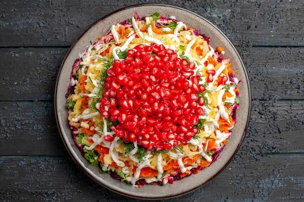 Widok z góry z bliska sałatka bożonarodzeniowa sałatka bożonarodzeniowa z ziemniakami, marchewką, burakami na białym talerzu na stole