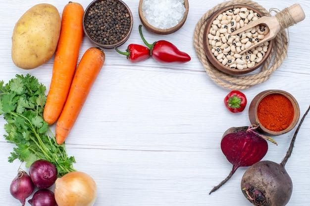 Widok z góry z bliska składu warzyw ze świeżych warzyw, surowej fasoli, marchwi i ziemniaków na lekkim biurku