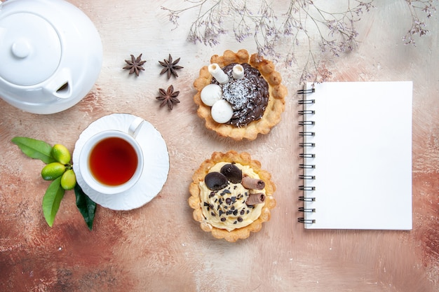 Widok z góry z bliska słodycze babeczki czajniczek filiżanka herbaty notatnik