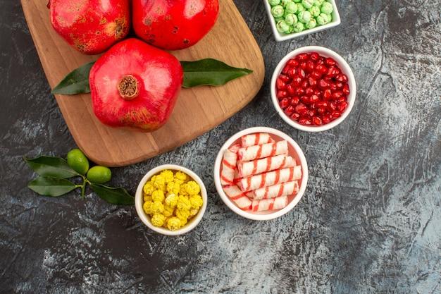 Widok z góry z bliska słodycze kolorowe słodycze granaty na desce do krojenia owoce cytrusowe