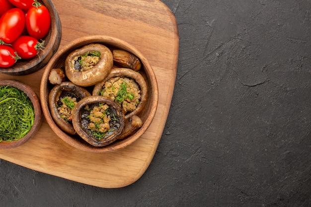 Widok z góry z bliska smaczne gotowane grzyby z czerwonymi pomidorami na ciemnym stole dojrzałe dzikie jedzenie