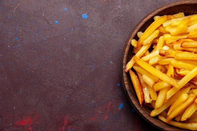 Widok z góry z bliska smażone ziemniaki smaczne frytki wewnątrz talerza na ciemnej powierzchni potrawa danie obiadowe składniki potrawy produkt ziemniak