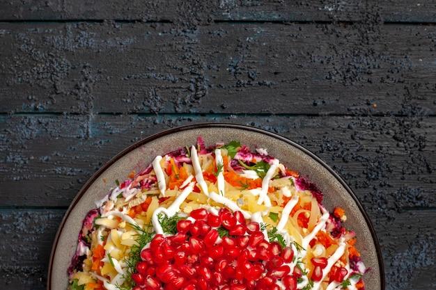 Widok z góry z bliska świąteczne danie apetyczne świąteczne danie z nasionami granatu w talerzu na ciemnej powierzchni