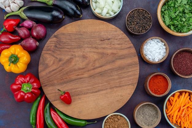 Widok z góry z bliska świeże warzywa z przyprawami i zielenią na ciemnym biurku sałatka jedzenie posiłek przekąska warzywna