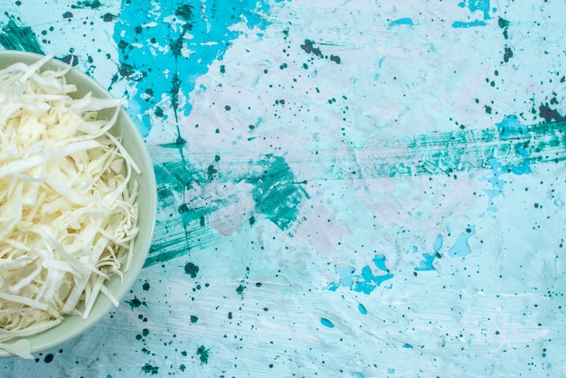 Widok z góry z bliska świeżej kapusty pokrojonej w plasterki wewnątrz okrągłej płyty na jasnoniebieskim, warzywnym posiłku zdrowej sałatki
