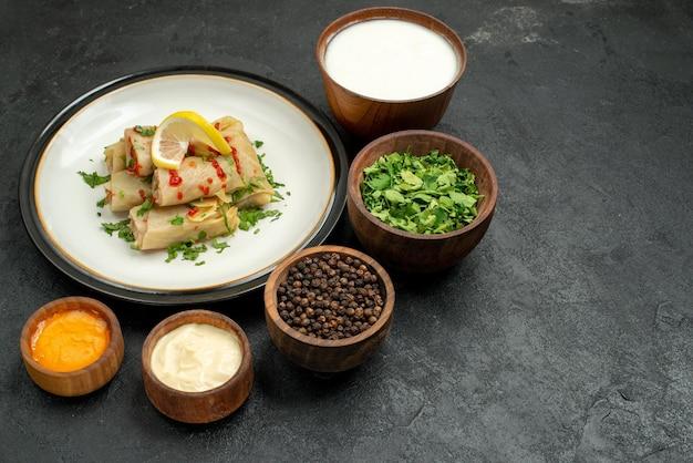 Widok z góry z bliska talerz jedzenia biały talerz gołąbki z ziołami cytryna i sos i miski z czarnym pieprzem z kwaśną śmietaną biały i żółty sos i zioła na czarnym stole