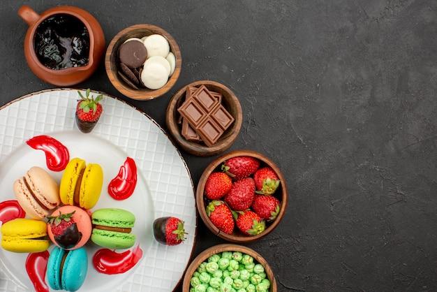 Widok z góry z bliska talerz słodyczy truskawki w czekoladzie makaroniki francuskie na talerzu pięć misek słodyczy na stole